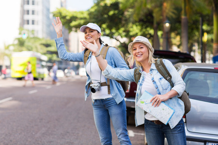 hailing: two tourists calling for a taxi in the city