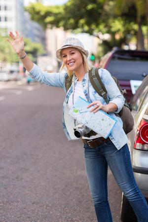 hailing: pretty tourist hailing a cab in the street
