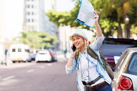 hailing: female tourist hailing a taxi in the city Stock Photo