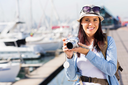 portrait of pretty female tourist standing at the harbour photo