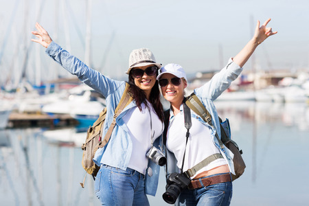 happy female tourists enjoying their vacation by the harbor photo