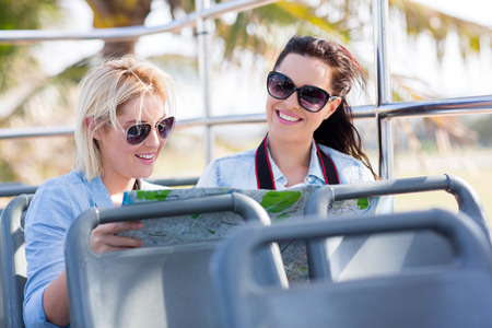 female tourists travelling on a open top bus and looking at a map photo