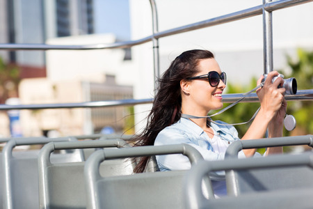 taking video: female traveller taking video of the city using digital camera from an open top bus Stock Photo