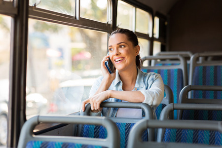 beautiful female commuter talking on cell phone while taking bus to work photo
