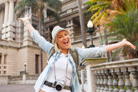cheerful tourist arms up in front of historical building photo