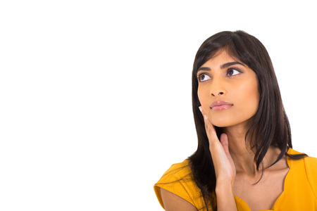 portrait of thoughtful indian woman looking up on white background photo
