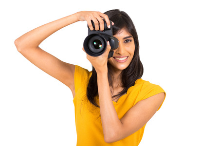 cheerful young indian woman taking pictures in studio with dslr photo
