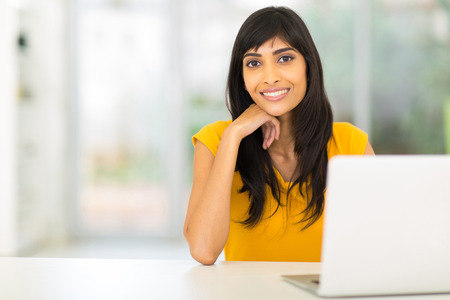 relaxed woman: portrait of pretty indian woman sitting in front of laptop