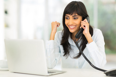 indian professional: happy indian businesswoman receiving exciting news over the phone