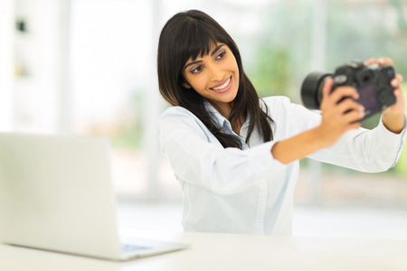 happy indian female photographer taking a selfie photo