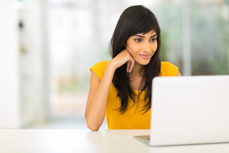 at home: attractive young indian woman looking at the laptop screen Stock Photo