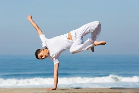 dancing girl: female dancer practicing handstand on beach