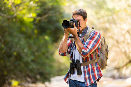 young photographer taking photos in mountain valley