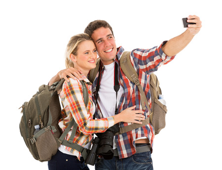 happy couple white background: cheerful couple tourists taking selfie with smart phone
