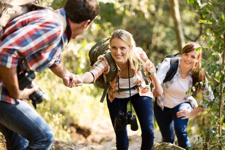 ayudando: joven ayudando a amigos para subir la roca