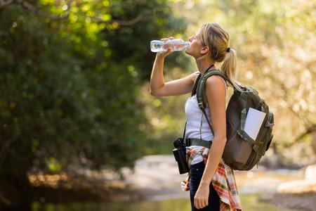 tomando agua: joven excursionista de agua potable en el valle de montaña Foto de archivo