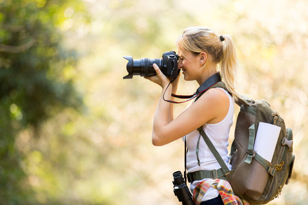 young female photographer taking photos in mountain valley photo