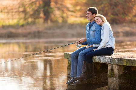 snuggle: peaceful young couple fishing by the pond in autumn