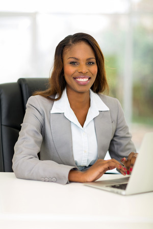 charming business lady: pretty african businesswoman using computer in office