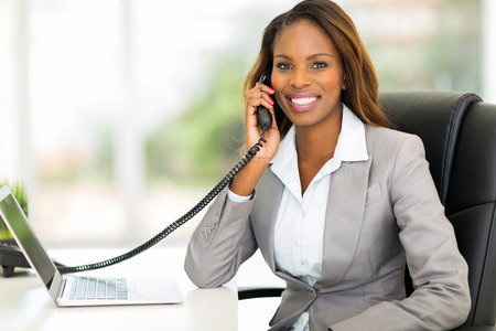 landline: attractive african american office worker talking on the phone Stock Photo