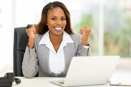 excited african american businesswoman waving fists in office