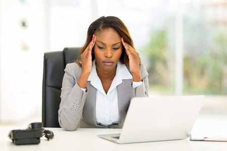 stressed african businesswoman sitting in office 스톡 콘텐츠