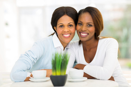 gorgeous woman: cute mid age african mother and adult daughter having tea at home