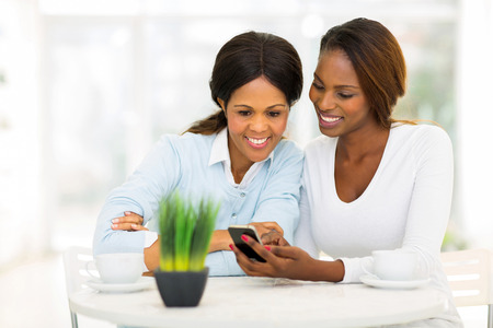 beautiful african mother and daughter using smart phone at home photo