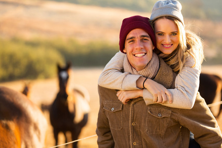 back country: happy woman enjoying piggyback ride on boyfriends back