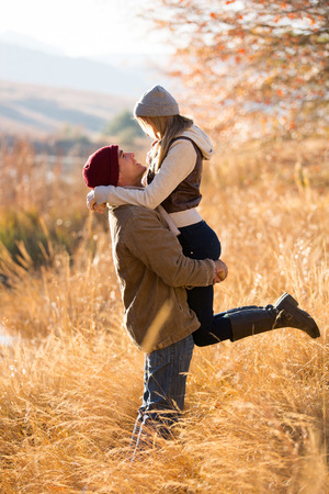 playful young man picking up his girlfriend by the lake in fall photo