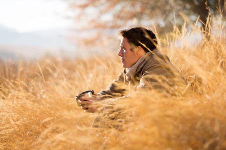 handsome man sitting in tall grass in autumn