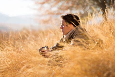 the nature of sunlight: handsome man sitting in tall grass in autumn