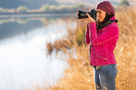 beautiful photographer take photo outdoors by the lake in autumn photo