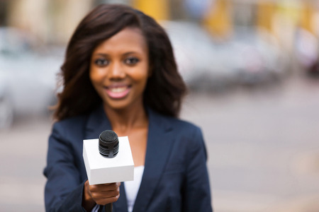journalists: portrait of young african female journalist interviewing people on street Stock Photo