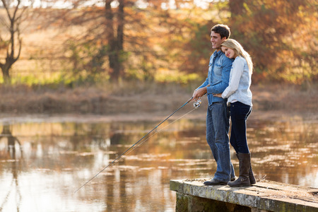 lovely young couple fishing together by a lake