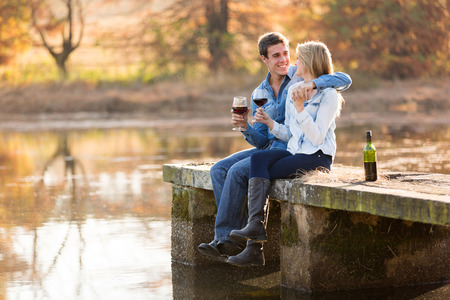 happy young couple drinking red wine by the lake photo