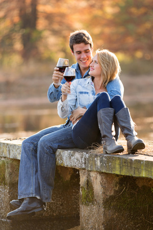 romantic couple drinking red wine outdoors photo