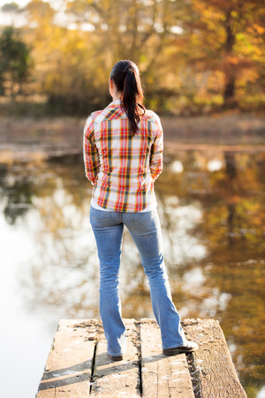 woman back view: back view of peaceful young woman standing on lake pier in fall