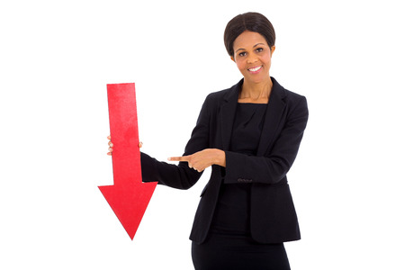 mature african businesswoman holding red arrow pointing down on white background photo