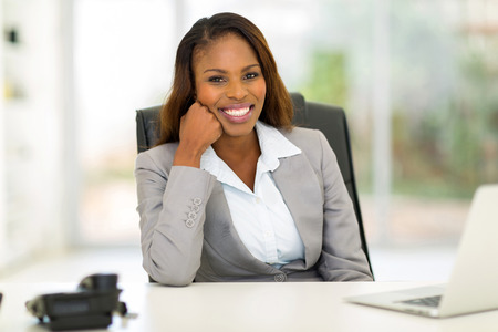african american businesswoman: portrait of happy young african businesswoman sitting in office Stock Photo