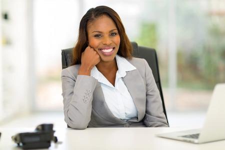 mujer alegre: retrato de la joven empresaria feliz africano sentado en la oficina Foto de archivo