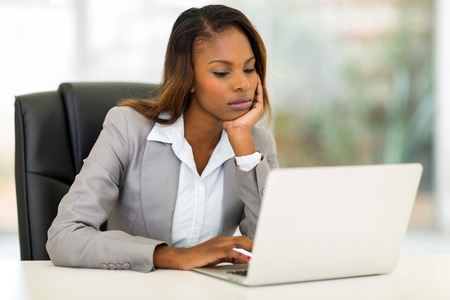 thoughtful young african businesswoman looking at the laptop screen photo