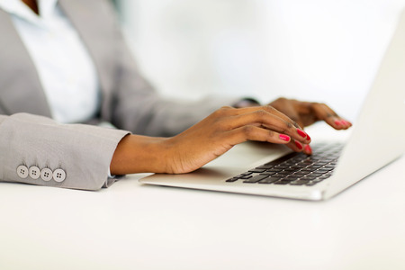 close up of african businesswoman hands working on laptop photo