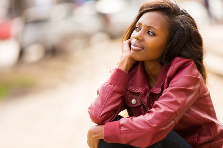 woman pose: cute young african woman daydreaming outdoors