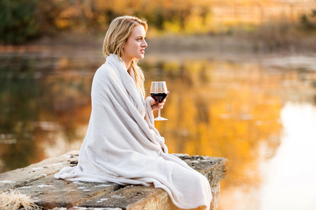 thoughtful woman with a glass of red wine sitting on pier  photo
