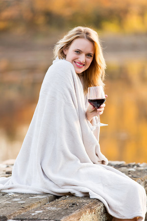 pretty woman sitting on a pier and enjoying wine at sunset photo
