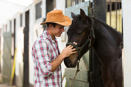 horse stable: young horse breeder comforting a horse in stable Stock Photo