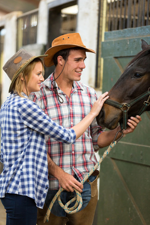 caring cowboy and cowgirl in stable touching a horse photo