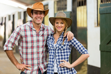 portrait of cowboy cowgirl couple inside stable photo