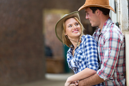 happy young farm couple embracing in stables photo